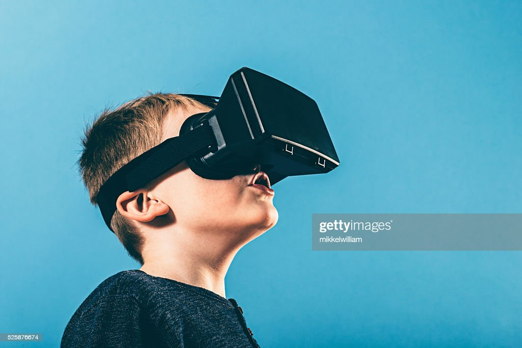 Boy is surprised by content on VR glasses : Stock Photo