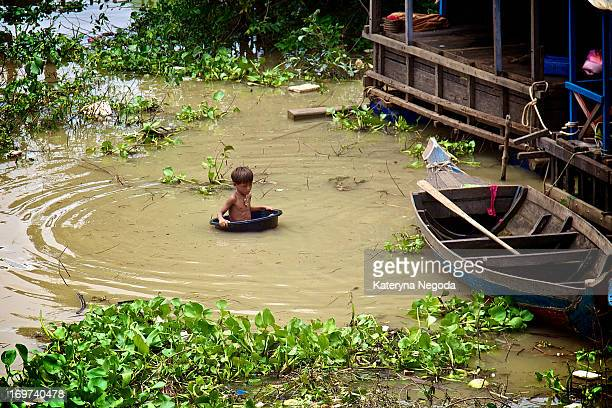 Boy is swimming in a washbowl in Tonle Sap Floating Village , Cambodia