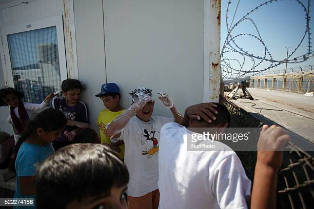 A boy is washing his hair in a faucet Refugee camp in Skaramaga area a port town 11 km west of Athens A large camp is being constructed here with a...
