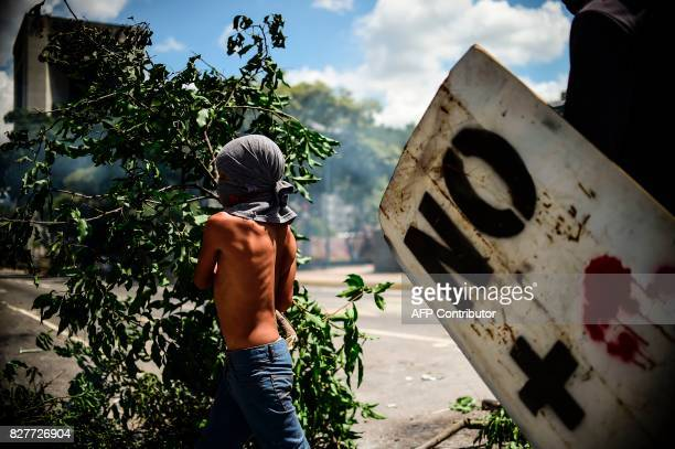 TOPSHOT A boy joins antigovernment activists protesting against Venezuelan President Nicolas Maduro at a barricade set up on a road in Caracas on...