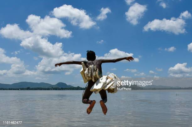 Boy jump in the Brahmaputra river wearing polystyrene sheets to keep himself afloat in the water during a hot summer day, in Guwahati, Assam, India...