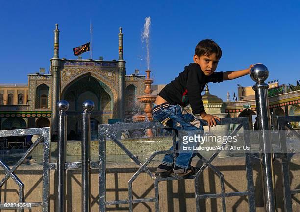 Boy jumping a fence in Fatima alMasumeh shrine Central County Qom Iran on October 8 2016 in Qom Iran