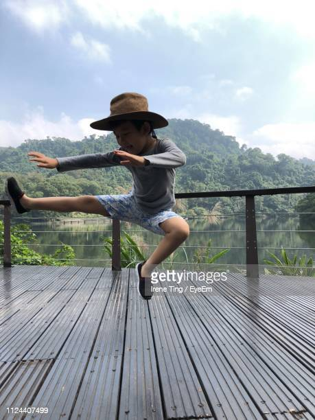 Boy Jumping At Observation Point Against Mountain