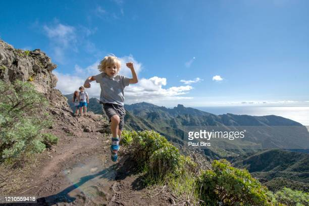 boy jumping for joy on a dirt trail, the mountain of baracan in the teno range, tenerife, canary islands, spain - fesse enfant photos et images de collection