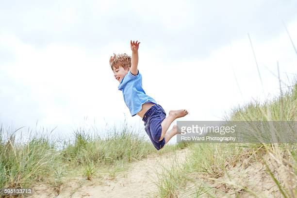 boy jumping from a sand dune - leap of faith stock photos and pictures