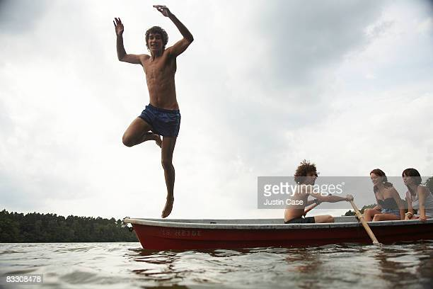 Boy jumping from boat into water