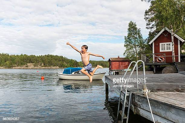 Boy jumping from jetty