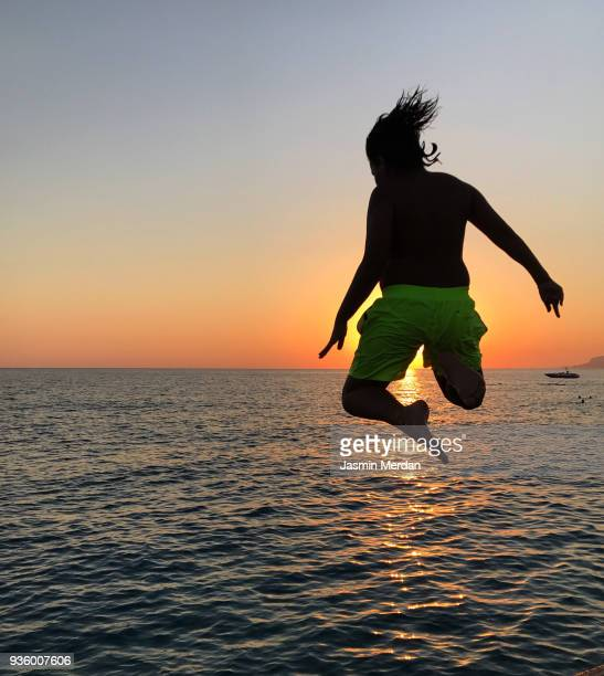 Boy jumping from jetty to sea on beach