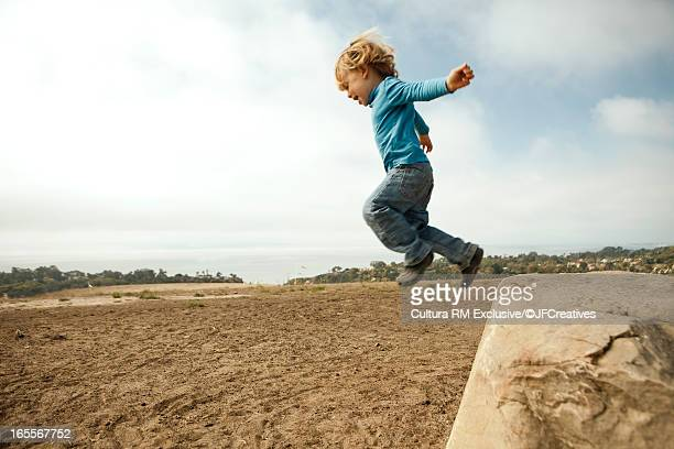 Boy jumping from rock into dirt