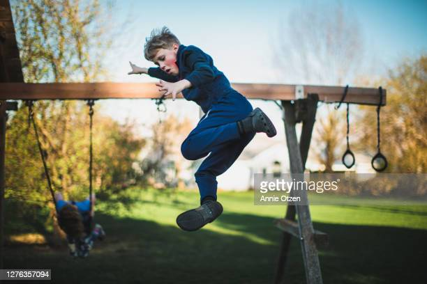 boy jumping from swing set - stunt stock pictures, royalty-free photos & images