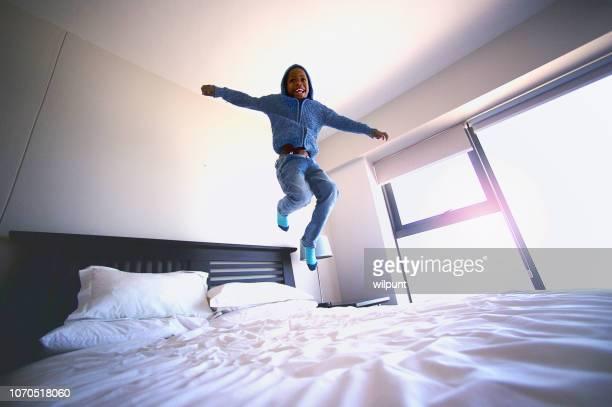 jongen hoog springen van vreugde, op een bed lage hoekmening - alleen één jongen stockfoto's en -beelden