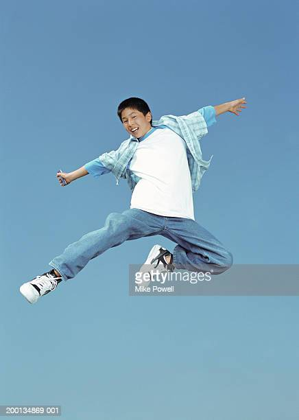 Boy (12-14) jumping in air, holding mobile phone, low angle