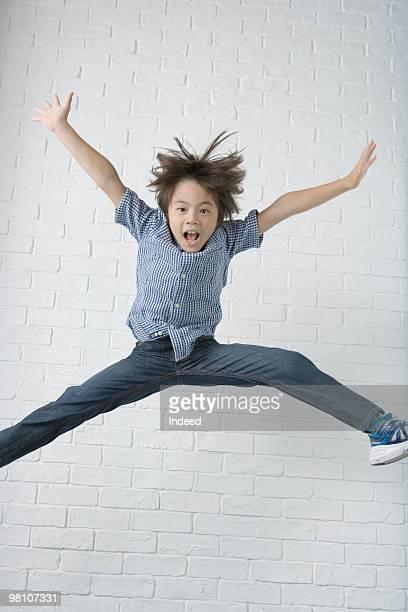 boy (8-9) jumping in air - 足を開く ストックフォトと画像