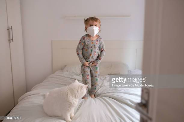boy jumping in bed next to the cat wearing surgical mask - funny surgical masks stock pictures, royalty-free photos & images