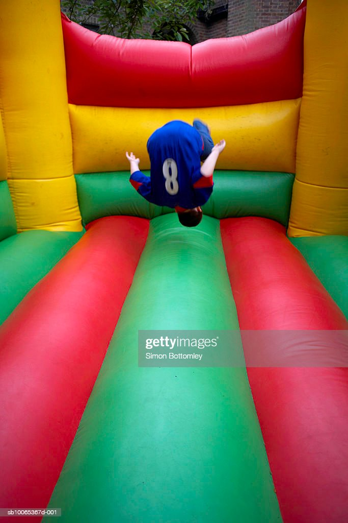 Boy (13-14) jumping in bouncy castle : Foto stock