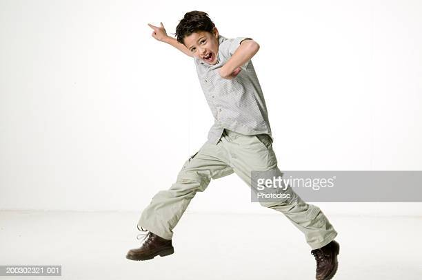 Boy (8-9) jumping in empty room