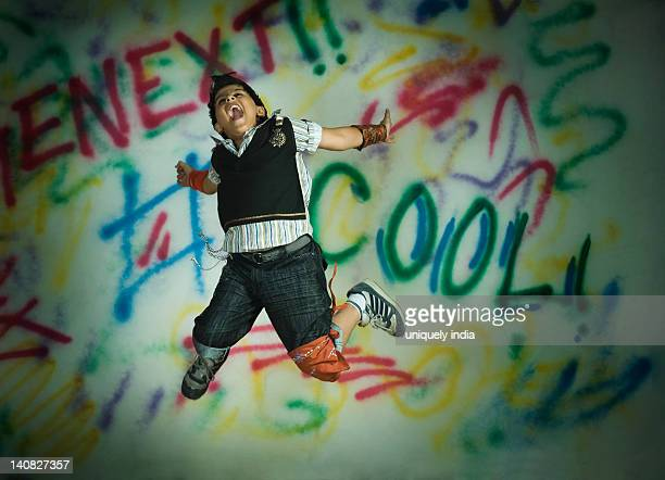 Boy jumping in front of a graffiti covered wall
