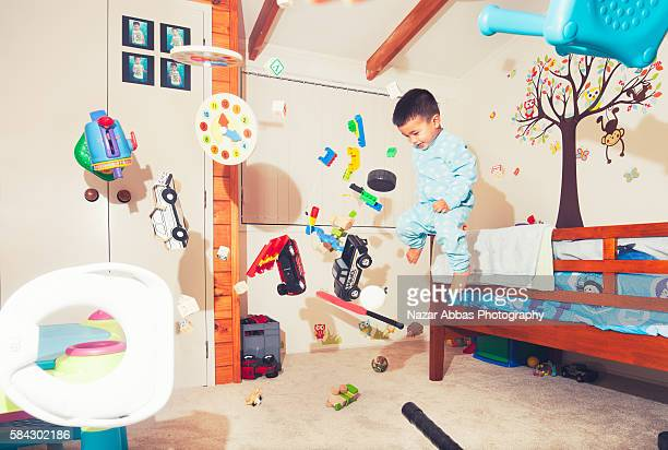Boy jumping in his room.