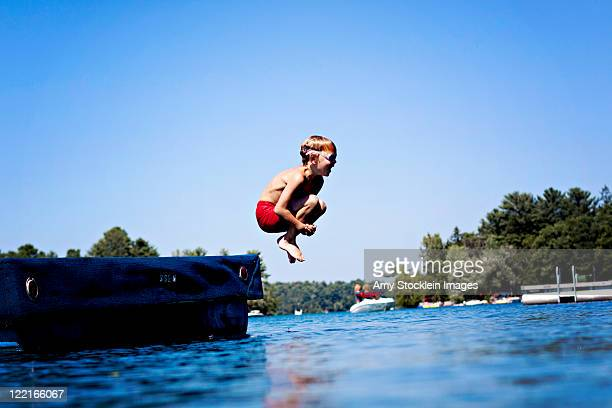 Boy jumping in lake