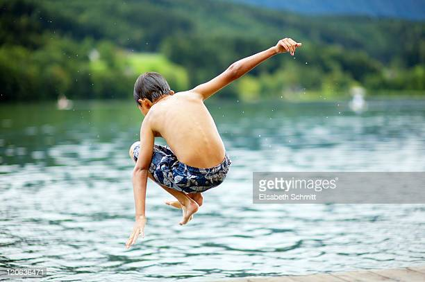 Boy jumping in lake, view from back