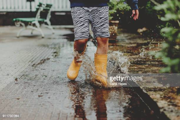 boy  jumping in large water puddle in early spring - rubber boot stock pictures, royalty-free photos & images