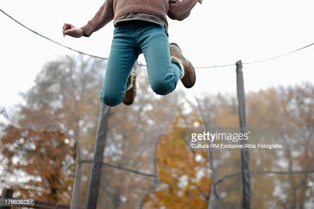Boy jumping in mid air, low section