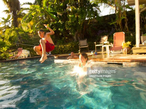 boy jumping in pool - cannon stock pictures, royalty-free photos & images