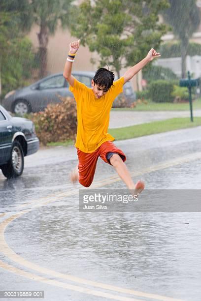 Boy (10-12) jumping in rain
