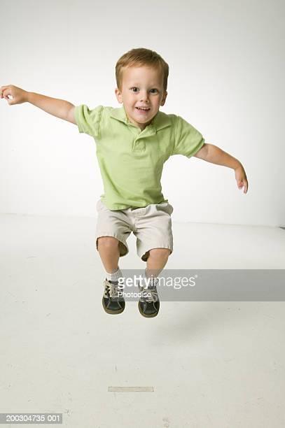 Boy (4-5), jumping in studio, portrait