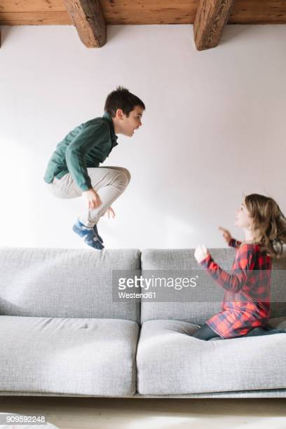 boy jumping in the air on the couch while his sister watching him - sister stock pictures, royalty-free photos & images