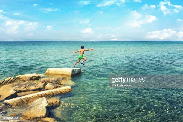 boy jumping in the sea - thasos stock photos and pictures