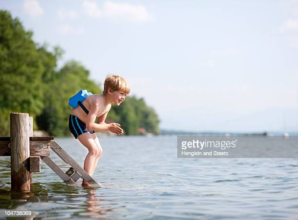 Boy jumping in water with swimming belt