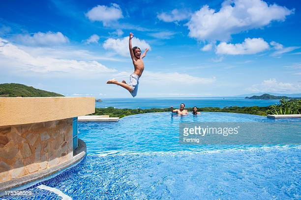 Boy jumping into a swimming pool in Costa Rica