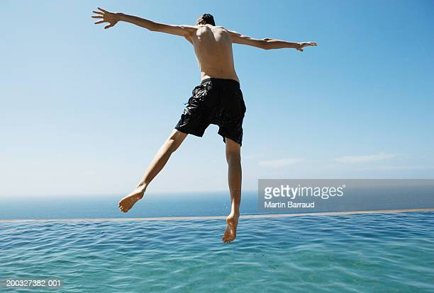 Boy (9-11) jumping into infinity pool, arms outstretched, rear view