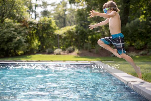 Boy jumping into outdoor swimming pool