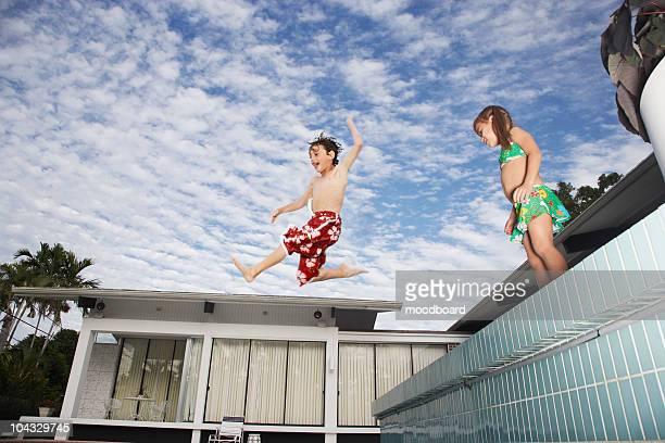 Boy (7-9) jumping into pool, girl (5-6) watching