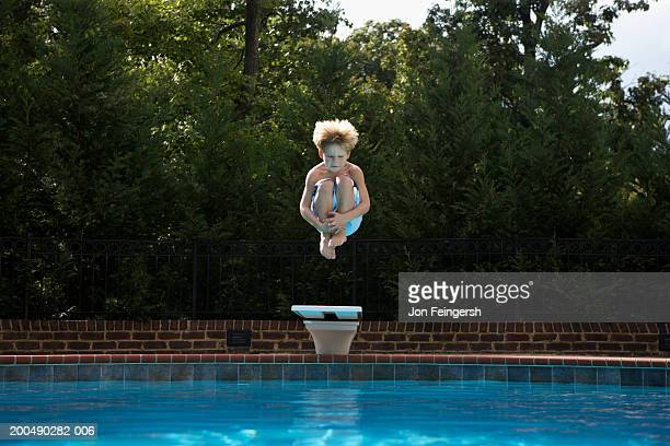 Boy (5-7) jumping into pool