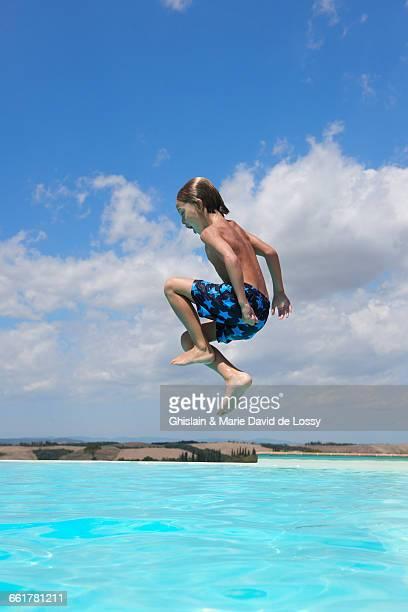 Boy jumping into swimming pool, Buonconvento, Tuscany, Italy