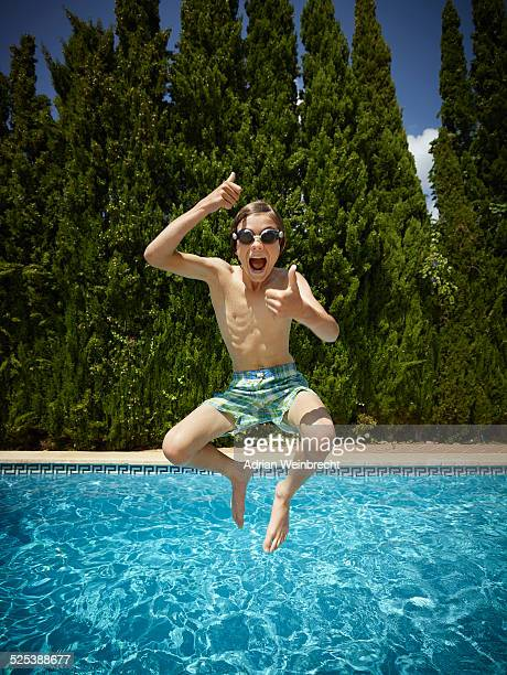 Boy jumping into swimming pool, Majorca, Spain
