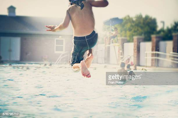 Boy jumping into the pool.