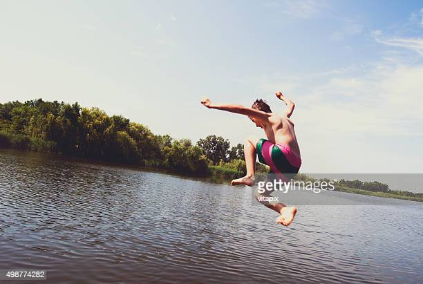 Boy jumping into the river