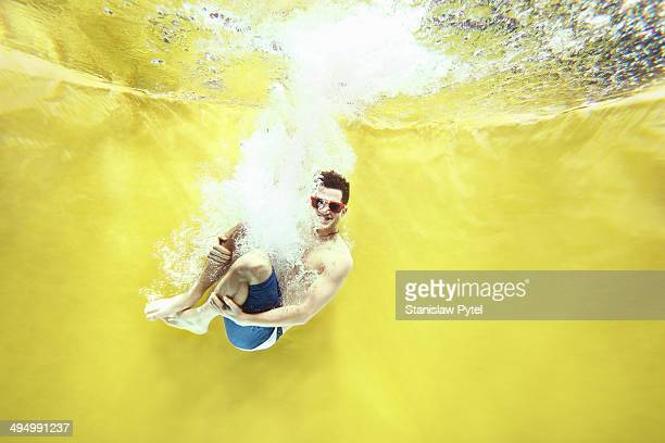 Boy jumping into water on yellow background