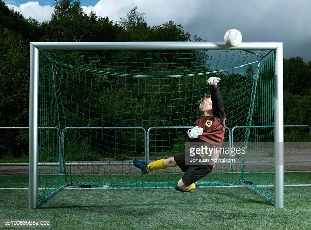 boy (8-9 years) jumping mid air catching ball at goal post - guarda redes imagens e fotografias de stock