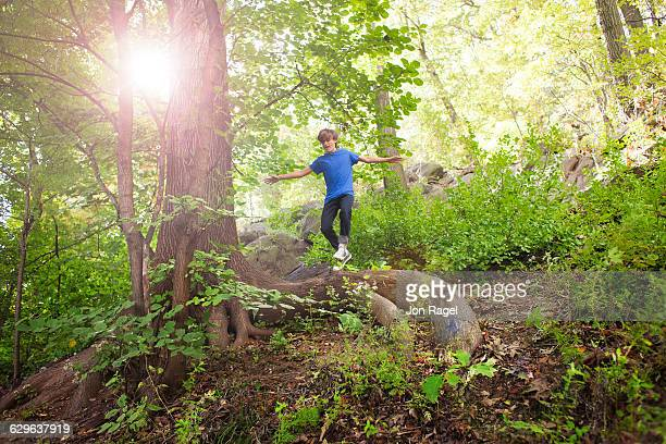 Boy jumping off a tree in the forest