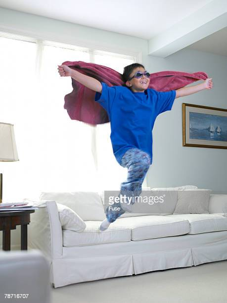 Boy Jumping Off Couch Playing Superhero