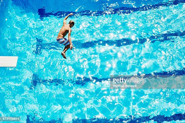 Boy jumping off diving board into outdoor pool