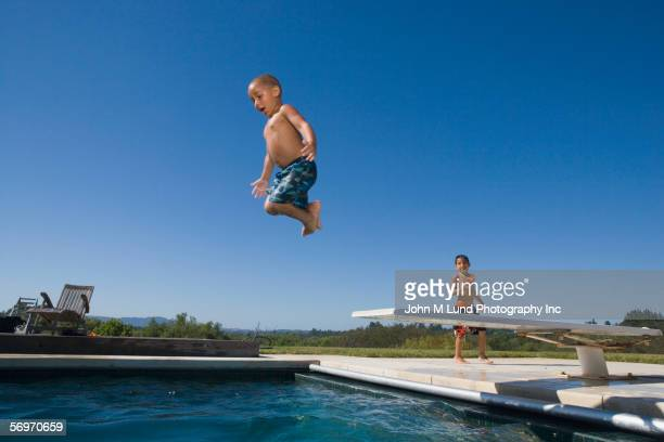 Boy jumping off diving board into pool