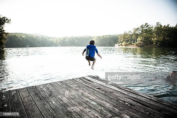 boy jumping off dock into lake - georgia verenigde staten stockfoto's en -beelden