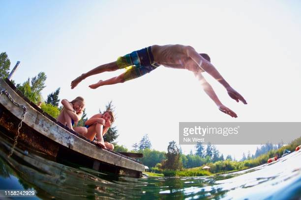 boy jumping off dock into sunny summer lake - wide angle stock pictures, royalty-free photos & images