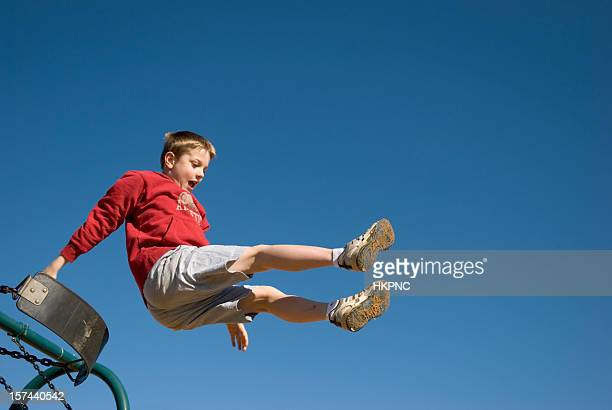 boy jumping off swing with clear blue sky - play off stock pictures, royalty-free photos & images